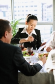 Executives looking at documents over lunch - Asia Images Group
