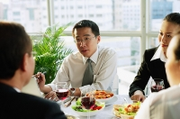 Businessmen and women, talking over lunch - Asia Images Group