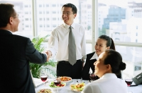 Businessmen shaking hands over lunch table, businesswomen sitting next to them - Asia Images Group