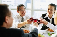Executives at restaurant, toasting with wine - Asia Images Group