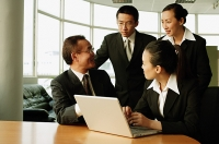 Executives having a discussion in office, laptop open on table - Asia Images Group