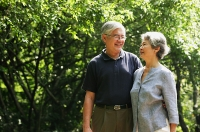 Senior couple standing in park, side by side, smiling - Asia Images Group