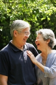 Senior couple facing each other, smiling - Asia Images Group