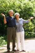 Senior couple looking up, hands outstretched - Asia Images Group