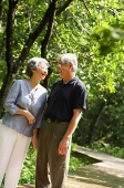 Senior couple standing, facing each other, smiling - Asia Images Group