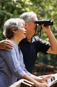 Senior couple side by side, man using binoculars - Asia Images Group
