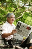 Senior man reading newspaper - Asia Images Group