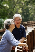 Mature couple side by side, smiling, woman looking up - Asia Images Group