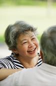Mature woman smiling at man, portrait - Asia Images Group