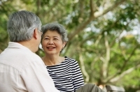 Mature couple facing each other, woman smiling - Asia Images Group