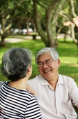 Mature couple sitting in park, facing each other, man smiling - Asia Images Group