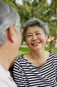 Mature couple facing each other smiling, woman wearing striped shirt - Asia Images Group