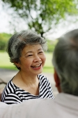 Mature couple facing, woman wearing striped shirt, smiling - Asia Images Group