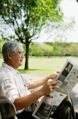 Senior man reading newspaper in park - Asia Images Group