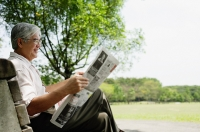 Senior man sitting on bench in park reading newspaper - Asia Images Group