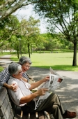 Couple in park, man reading newspaper, woman standing behind him looking over shoulder - Asia Images Group