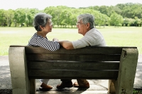 Mature couple sitting face to face on park bench - Asia Images Group