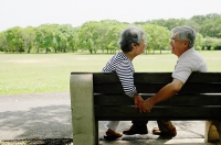 Mature couple sitting face to face on park bench, holding hands - Asia Images Group