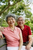 Mature couple on park bench, looking at camera - Asia Images Group