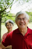 Mature man, looking at camera, woman standing behind him - Asia Images Group