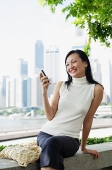 Young woman, looking at mobile phone, smiling - Asia Images Group
