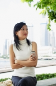 Young woman, holding mobile phone, arms crossed - Asia Images Group