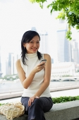 Young woman, holding mobile phone, looking at camera - Asia Images Group