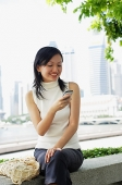 Young woman, using mobile phone, text messaging - Asia Images Group