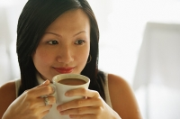 Young woman, holding cup of coffee, looking away - Asia Images Group