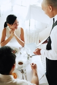 Waiter showing menu to couple at restaurant - Asia Images Group