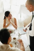 Waiter showing menu to couple at restaurant, woman smiling at him - Asia Images Group