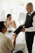Couple in restaurant, man handing menu back to waiter - Asia Images Group