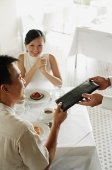Man giving menu to waiter, woman sitting opposite him - Asia Images Group