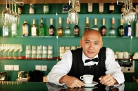 Bartender behind bar counter, with cup and saucer - Asia Images Group