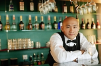 Bartender behind bar counter, glass of water in front of him - Asia Images Group