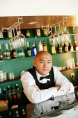 Bartender behind bar counter, arms crossed - Asia Images Group