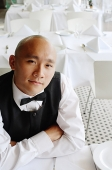 Waiter sitting at table, arms crossed, looking at camera - Asia Images Group