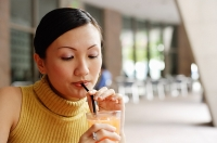 Woman drinking from straw - Asia Images Group
