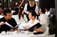Couple in restaurant, looking at menus - Asia Images Group