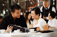 Couple in restaurant, holding menu and smiling at each other - Asia Images Group