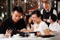 Couple in restaurant, looking through menu - Asia Images Group