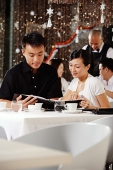 Couple in restaurant, looking through menu, people in the background - Asia Images Group