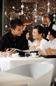 Couple in restaurant, holding menu, smiling at each other - Asia Images Group