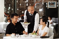 Waiter serving couple at restaurant - Asia Images Group