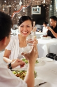 Couple at restaurant, holding glasses of water, over the shoulder view - Asia Images Group