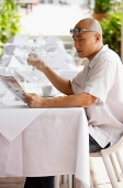 Man sitting at table, reading newspaper, holding glass of water - Asia Images Group