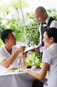 Couple in restaurant, making payment to waiter - Asia Images Group