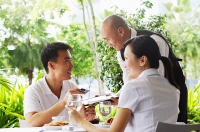 Couple in restaurant, man giving waiter credit card - Asia Images Group