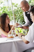 Couple in restaurant, woman making payment to waiter - Asia Images Group