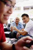 Two men toasting with drinks, looking at camera, another man using mobile phone in the foreground - Asia Images Group